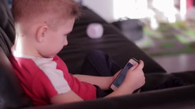 Young boy playing game on smartphone in home stock video