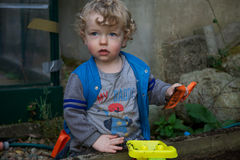 Young boy playing in garden. Young blond haired boy playing with plastic garden tools outdoors royalty free stock photo