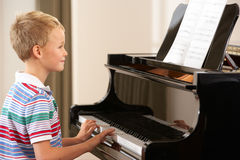Young boy playing grand piano Stock Photo