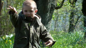Young boy playing with grass in the backyard 01 stock footage