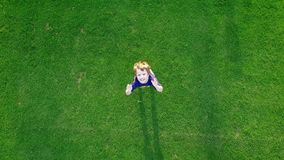 Young boy playing on the green grass stock footage