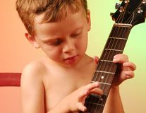 Young boy playing guitar Royalty Free Stock Images