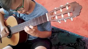 Young boy playing the guitar stock video