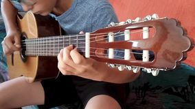Young boy playing the guitar stock video footage