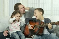 Portrait of boy playing the guitar for his family. Young boy playing the guitar for his family stock photos