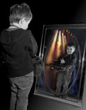 Young boy playing guitar in mirror. stock photos