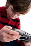 Young boy playing handheld game console. Isolated on white background Royalty Free Stock Photo