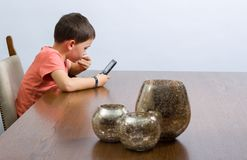 Boy playing video game. Young boy playing handheld video game at a table with some decoration. Against grey background royalty free stock photo