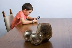 Boy playing video game. Young boy playing handheld video game at a table with some decoration. Against grey background stock photos