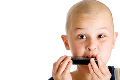 Young boy playing harmonica Stock Photos