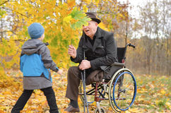 Young boy playing with his disabled grandfather Royalty Free Stock Photo