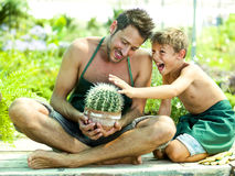 Young boy playing with his father in a greenhouse royalty free stock images