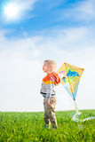 Young boy playing with his kite in a green field Stock Photography