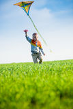 Young boy playing with his kite in a green field Stock Image