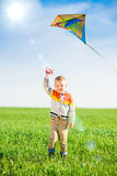 Young boy playing with his kite in a green field Stock Photos