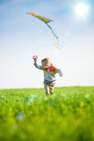 Young boy playing with his kite in a green field. Royalty Free Stock Photo