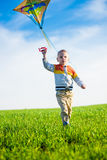 Young boy playing with his kite in a green field. Royalty Free Stock Photos