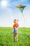 Young boy playing with his kite in a green field. Royalty Free Stock Photography