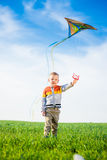 Young boy playing with his kite in a green field. Royalty Free Stock Images