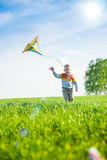 Young boy playing with his kite in a green field. Stock Images
