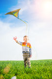 Young boy playing with his kite in a green field. Royalty Free Stock Image