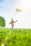 Young boy playing with his kite in a green field. Stock Photo