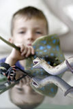 Young boy playing. With his plastic animals at home Royalty Free Stock Photos