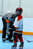 Young boy playing hockey. Young Boy playing indoor roller hockey with referee in background Royalty Free Stock Image