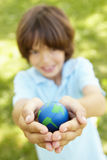 Young Boy Playing Holding Model Of Globe In Park Stock Photography