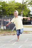 Young boy playing hopscotch Royalty Free Stock Photography