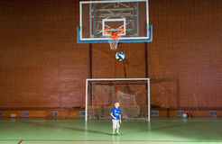 Young boy playing indoor soccer. Standing in the goalposts watching as a ball loops through the air towards the goal Stock Image