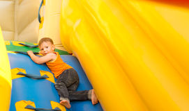Young boy playing in an inflatable slide Royalty Free Stock Images