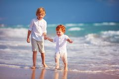 Young boy playing with junior brother on sandy beach Stock Photos