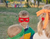 Young boy playing at a kids birthday party. Wearing a super hero mask as he chats to his young friends Royalty Free Stock Image