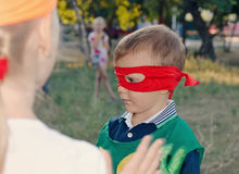 Young boy playing at a kids birthday party. Wearing a super hero mask as he chats to his young friends Stock Photography
