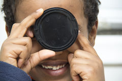 Young boy playing with a lens cover Royalty Free Stock Photos