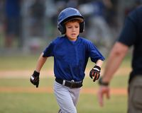 Young boy playing Little League Baseball. Little league baseball player during a YMCA baseball game. Cute boy in blue and grey uniform stock photos