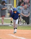 Young boy playing Little League Baseball. Little league baseball player during a YMCA baseball game. Cute boy in blue and grey uniform royalty free stock images