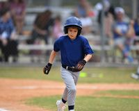 Young boy playing Little League Baseball. Little league baseball player during a YMCA baseball game. Cute boy in blue and grey uniform royalty free stock image