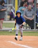 Young boy playing Little League Baseball. Little league baseball player during a YMCA baseball game. Cute boy in blue and grey uniform royalty free stock photos