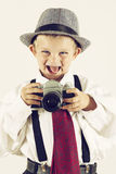 Young boy playing with an old camera to be photographer Royalty Free Stock Image