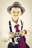 Young boy playing with an old camera to be photographer Royalty Free Stock Images