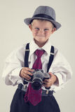 Young boy playing with an old camera to be photographer Royalty Free Stock Photo