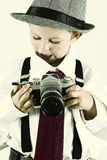 Young boy playing with an old camera to be photographer Stock Image