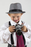 Young boy playing with an old camera to be photographer Stock Images