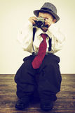 Young boy playing with an old camera to be photographer Royalty Free Stock Photos