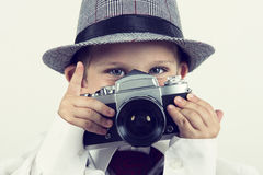 Young boy playing with old camera to be a photographer Stock Photo