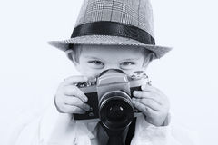 Young boy playing with old camera to be a photographer Stock Photography