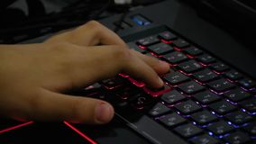 A young boy playing an online game on his personal computer. Close-up on his hand and fingers pushing the keyboard. A young boy playing an online game on his stock video