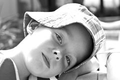Young boy playing in the park on a sunny day. Wearing sun hat Royalty Free Stock Photos